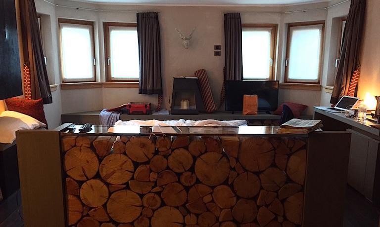 La stanza 103 del DV Chalet a Madonna di Campiglio in Trentino, con il letto matrimoniale al centro della camera, dettaglio che cambia completamente la percezione dello spazio da parte dell'ospite