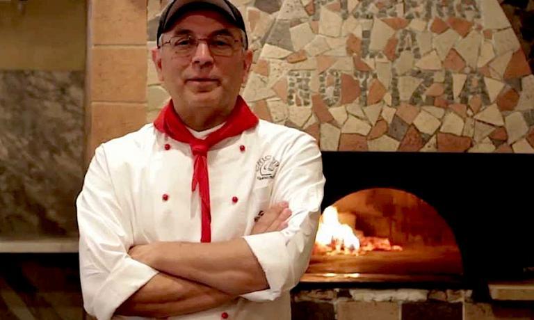 Enzo Coccia davanti al suo forno a legna in un'immagine di Italia Squisita. Sue a Napoli le due pizzerie chiamate La Notizia