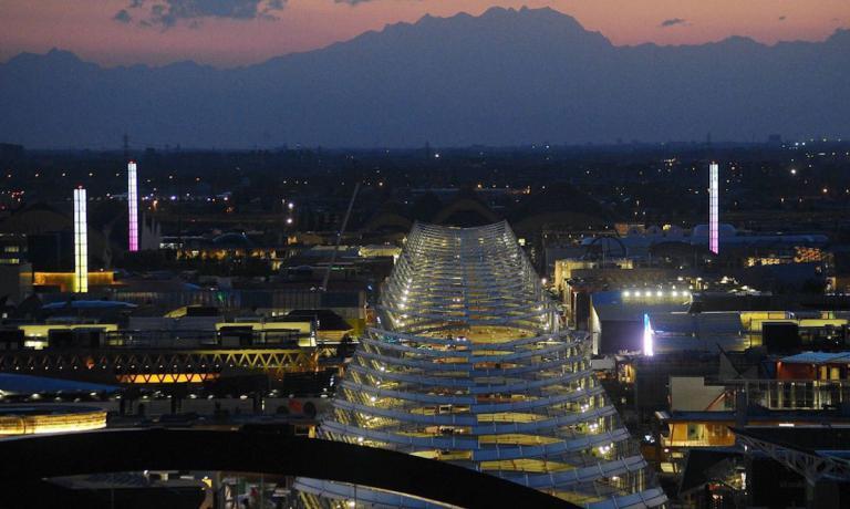 Nello scatto dell'agenzia Fotogramma, una emozionante e romantica veduta aerea del sito dell'Expo al tramonto. Ormai mancato tre giorni appena al via della seconda Esposizione Universale allestita a Milano. La prima risale al 1906 e aveva per tema i trasporti, allora solo quelli su rotaia