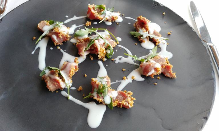 Tagliata di fassona impanata ma non cotta ai sentori di cioccolato bianco, salsa al parmigiano e rucola: è uno dei piatti di Antonio Borruso, nel suoUmami Restaurantdi Bormio, indirizzo prestigioso per l'alta cucina in Valtellina