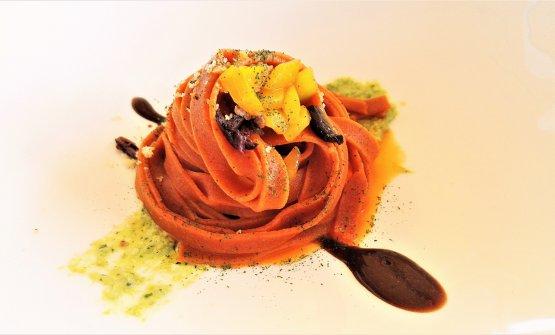 Nastrine di peperoni con alici, olive nere, pesto di peperoncini verdi di fiume, pistacchi su crema di aglio nero