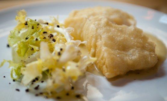 Filetto di baccalàislandese in pastella su crema di patate al limone, scarola riccia e olive itrane disidratate