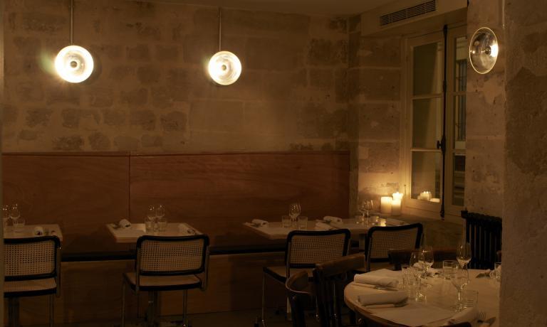 """Uno scorcio della salle à manger di Heimat, un luogo isolato nella pietra e la penombra, evocativo del sentimento di """"ritorno alle origini"""" della casa"""