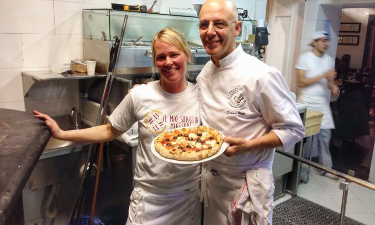 Sarah Minnick mostra con Franco Pepe la pizza che ha appena preparato usando solo ingredienti del territorio di Caiazzo: l'impasto a base di farina di grano Autonomia, mozzarella di bufala del caseificio Il Casolare di Alvignano, pomodoro riccio dell'azienda agricola La Sbecciatrice, origano del Matese, olive caiatine