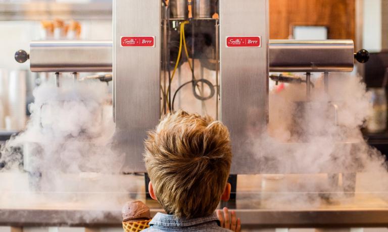 Un bimbo di fronte a due Brrr, le macchine per fare il gelato inventate da Robyn Sue Fisher: utilizzano l'azoto liquido