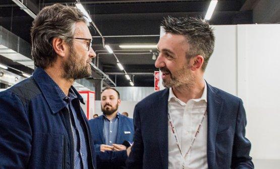 Andrea Balotelli, a destra, fotografato durante il Congresso 2019 di Identità Golose, mentre riceve la visita di Carlo Cracco allo stand Mepra
