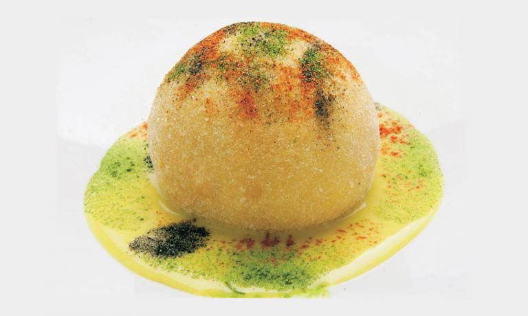 La Palla ThaidiRosannaMarziale, chef del ristorante Le Colonnedi Caserta. E'ripiena di spaghetti di riso, conditi con una salsa di latte di cocco, curry, zenzero, lime, funghi e peperoncino, racchiusi da una sfera di mozzarella rimozzata e poi fritta. I colori in superficie sonopolveri di pomodoro, prezzemolo, zafferano e olive