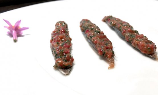 Alici marinate, tartare di rognone di coniglio, bietola, fiore di cipolla, burro morbido. Tutto giocato, come dice lo chef, sulla scioglievolezza
