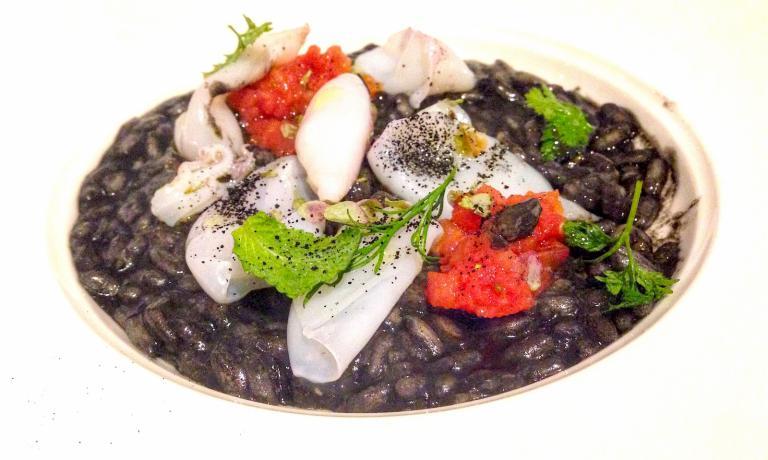 Il Risotto Carnaroli all'olio Nocellara con calamaretti spillo al nero, capperi di Pantelleria e profumo di limoni della Costiera di Negrini-Pisani