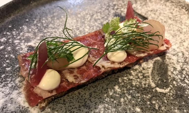 Paesaggio nordico: tartina croccante con vacca marinata, crema di formaggio affumicato, cipolla sottaceto, polvere di aceto di vino rosso