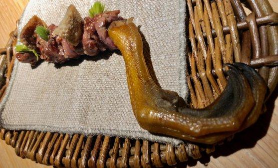 Duck feast #3: leg meat cooked on the bone Viene servito un spiedino di cosce d'anatra, con pelle croccante sopra.Pesto di formiche, gemme di pino mugo e burro d'alga