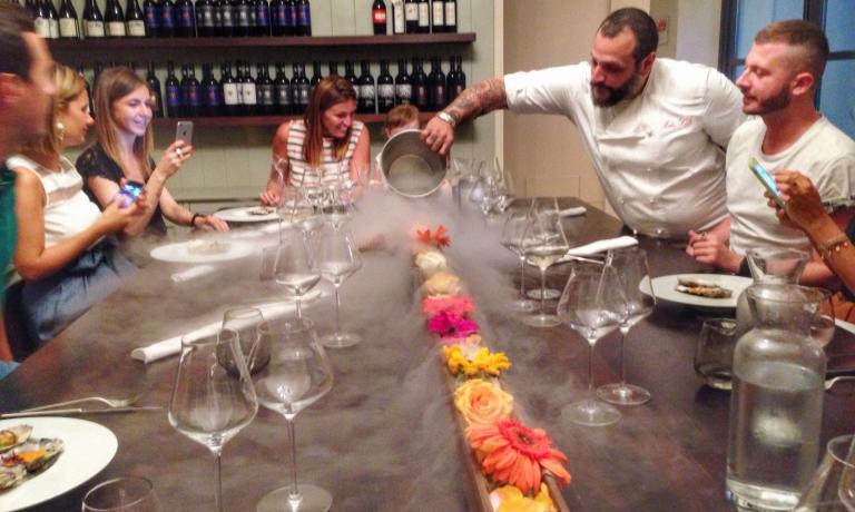 Al centro dell'unico tavolo, una lunga fioriera annaffiata...con l'azoto liquido