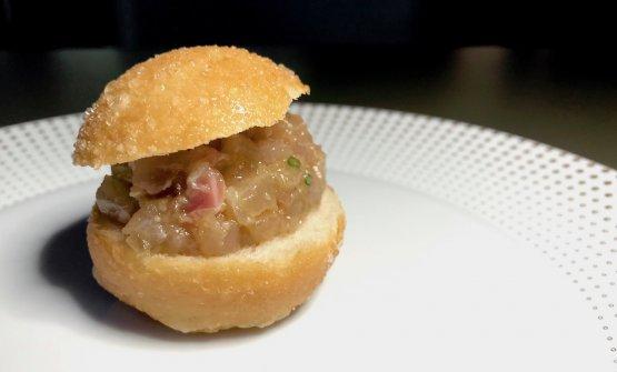 Panino, tartara di branzino selvaggio e salsa ponzu. Il panino è prima cotto al vapore e poi fritto delicatamente