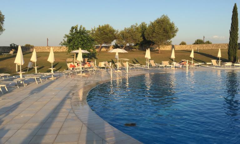 La piscina principale del complesso Acaya, circondata da muri in pietra e ulivi secolari