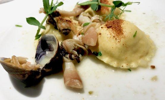 Ravioli alla spuma di ricciola, bottarga di tonno, vongole, cannolicchi, foglie di pisello