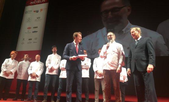 Il momento clou: Norbert Niederkoflerriceve la terza stella dalle mani del direttore internazionale delle Guide Michelin,Michael Ellis, sulla destra. Dietro di loro gli altri otto tristellati, tutti confermati