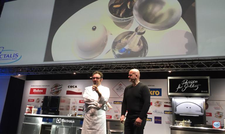 Lopriore e Andrea Salvetti sul palco di Madrid. Dietro di loro, un'immagine delle cozze cotte dallo chef nella Vaporiera di Salvetti stesso