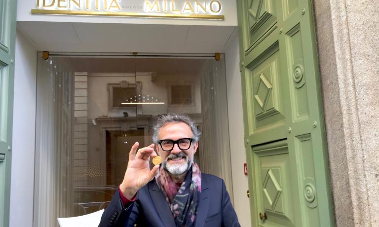 Massimo Bottura mostra la medaglia d'oro ricevuta dal Comune di Milano davanti all'entrata di Identità Golose Milano
