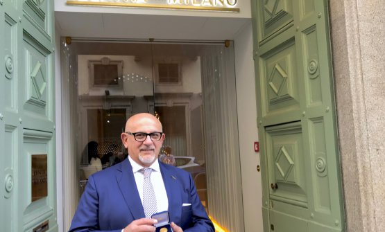 Claudio Sadler mostra la medaglia d'oro ricevuta dal Comune di Milano davanti all'entrata di Identità Golose Milano