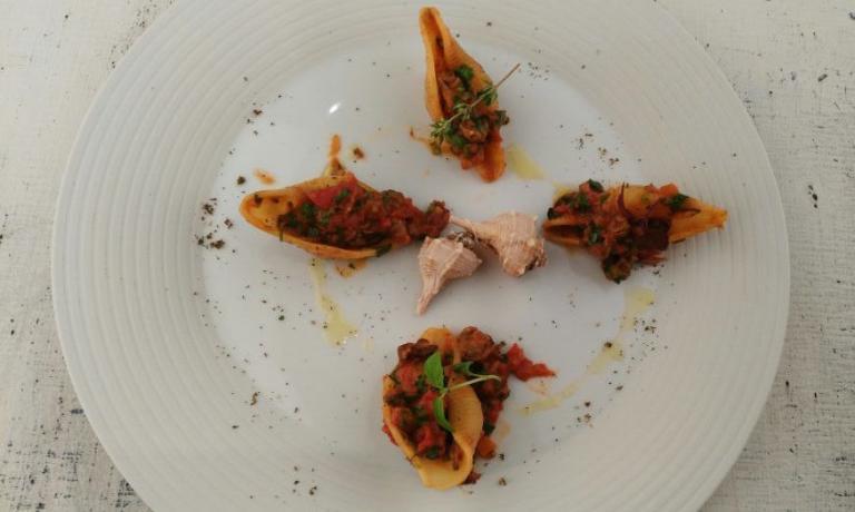 I Conchiglioni con conchiglie, primo piatto presentato ieri da�Fabrizio Mantovani, chef del bistrot Fm di Faenza (Ravenna) a Identit� Expo. E' un piatto che sa di Adriatico, d'ispirazione francese, in cui compare il murice, mollusco dalla conchiglia spinosa