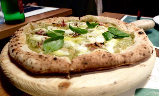 La pizza Macco, con macco di fave fresche, lo stesso fiordilatte, pancetta croccante di maialino nero casertano, pecorino di Laticauda, basilico fresco e olio evo Monti Iblei Dop