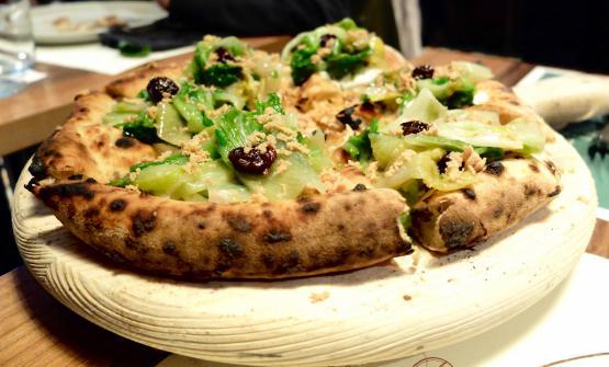 """La """"muscolosa"""" pizza Pasqualina, con topping a crudo di scarole novelle ripassate, granella di cucunci croccanti, uvetta di Pantelleria, pinoli tostati, burrata di Andria, bottarga di tonno rosso e olio evo varietà Nocellara del Belice"""