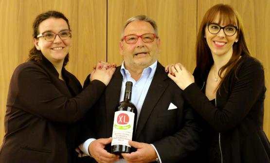 Fausto Maculan, al centro con la bottiglia di XL Quarantesima vendemmia, con le figlie Angela (a sinistra) e Maria Vittoria (a destra)