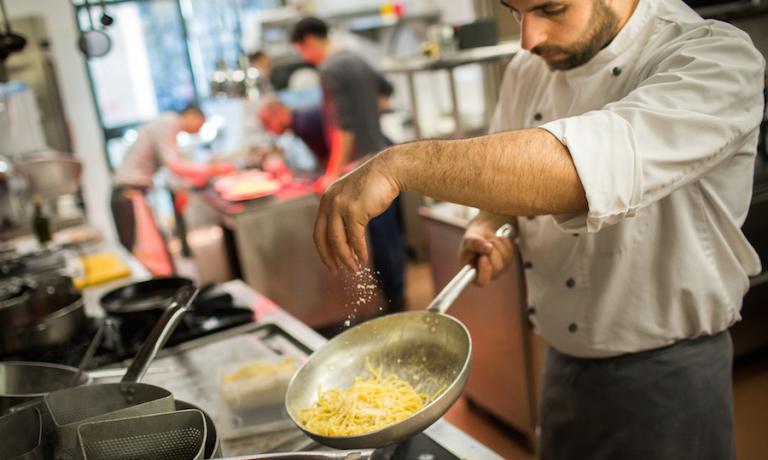 Un cuoco al lavoro nelal cucina di Marta in cucina a Reggio Emilia. La foto è di Niccolò Cozzi