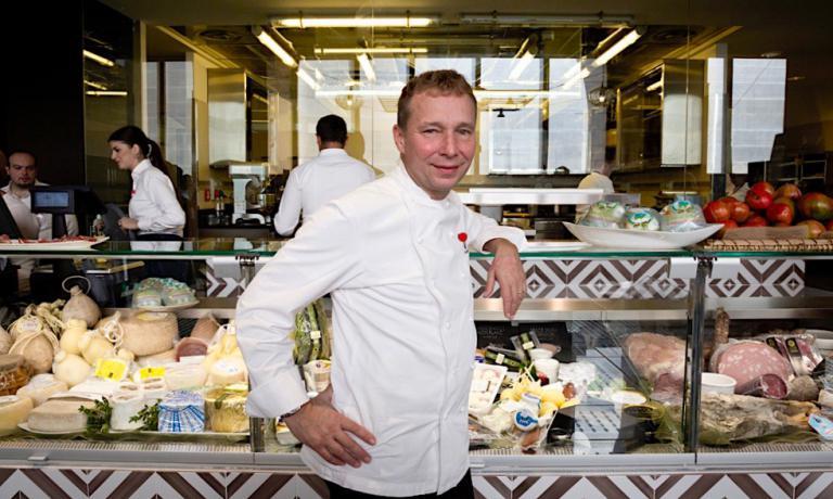 Oliwer Glowig di fronte al banco dei formaggi del