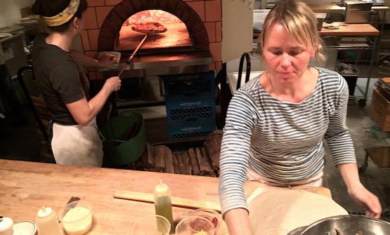 Mentre Sarah Minnick prepara una pizza, Emily Sguadra ne cuoce una nel forno