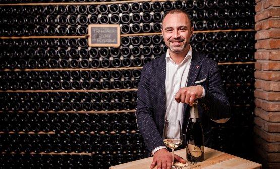 Alberto Schiavi mostra con orgoglio una bottiglia di Franciacorta Mirabella