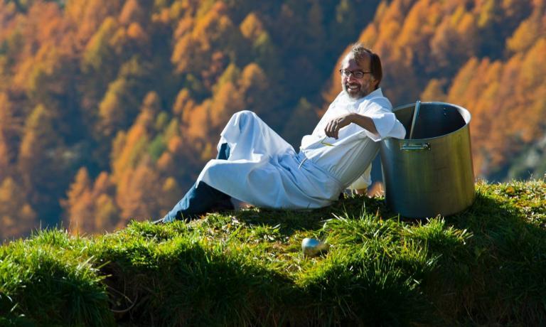 Norbert Niederkofler lying down among his pastures