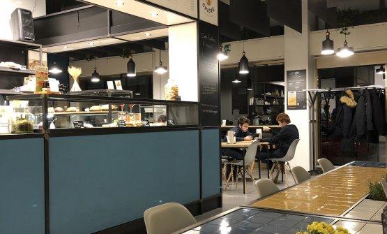 il laboratorio Chiere, con bancone e il tavolo convivialein primo piano. E'realizzato con materiali di recupero