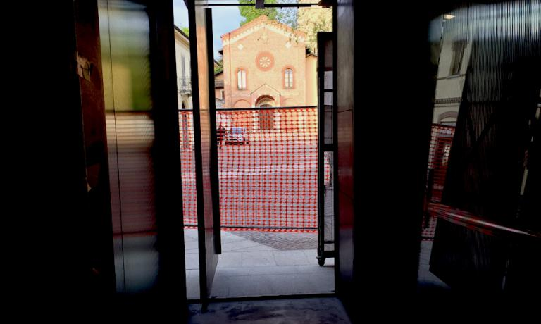 From inside the building site of the new D'O, right where there will be the crystal door, the telephone's lens pointed at sunset on Friday 15th April 2016 on the facade of the Chiesa Vecchia di San Pietro. The historic elm tree is in the middle of the square, between the restaurant and the place of worship