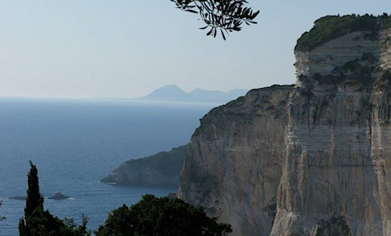 Se le spiaggie più accessibili di Paxos sono sulla costa orientale, quella che guarda la Grecia, nulla supera la spettacolarità della costa occiddentale, quella verso il mare aperto con le sue scogliere di oltre diecento metri a picco sul mare. La foto strega, sulla sfondo si distingue Corfù distante circa 24 km