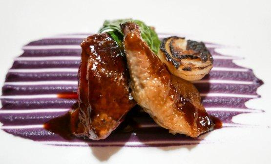 Piccione arrosto servito al sangue con cipolle alla brace, variazione di cavolo e salsa agrodolce piccante