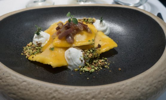 Ravioli con zucca, pistacchio tostato, ricotta mantecata e guanciale di suino nero croccante