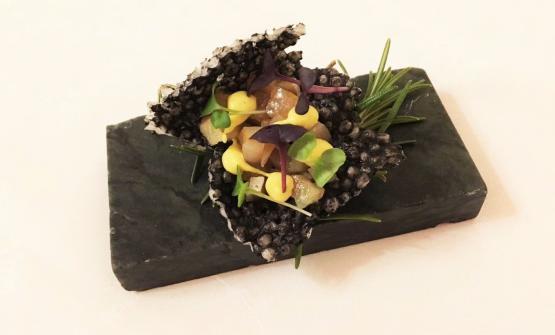SNACK.Tapioca soffiata al nero con sgombro, arancia e curry
