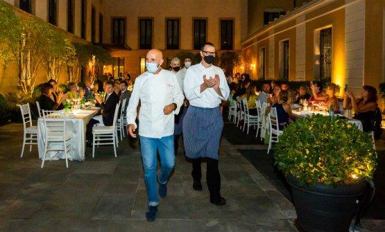 In primo piano, Andrea Ribaldone e Antonio Guida ricevono l'applauso del pubblico a fine cena, seguiti dalle brigate di sala e cucina