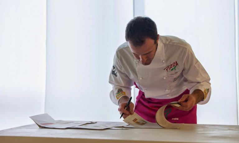 Simone Padoan chino sui libri: anche per il principe degli chef-pizzaioli lo studio non termina mai. Non a caso � uno dei simboli di questa nuova tendenza della pizza contamporanea d'autore che trova in PizzaUp il proprio luogo di sintesi e approfondimento annuale