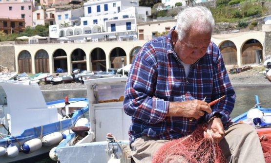 Un anziano pescatore ripara le reti nel porto di U
