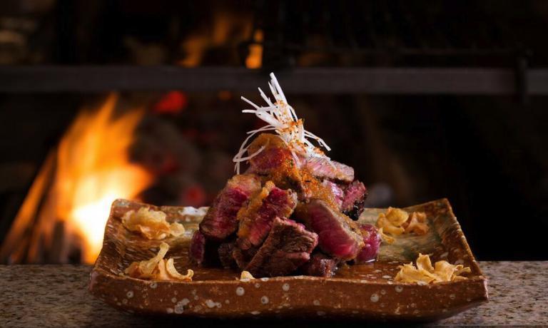 La Rib eye steak with wafu sauce and garlic crisps, il Filetto di manzo speziato piccante con semi di sesame, qui nella foto di John Carey, è uno dei signature dishes di Rainer Becker, proposto immancabilmente anche nel locale Zuma appena aperto a Roma