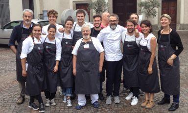La squadra di sala e cucina che ha lavorato ieri sera al Refettorio Ambrosiano in piazzale Greco, a Milano, un progetto di solidarietà che coinvolge alta cucina, arte e design. In casacca bianca, Massimo Bottura, chef dell'Osteria Francescana di Modenae anima del Refettorio. Alla sua sinistra Rene Redzepi, chef del Noma di Copenhagen, uno dei grandi cuochi inclusi nel programma. Tra i camerieri c'era anche Zanatta, autore del pezzo, invitato da Caritas