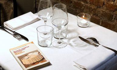 Un tavolo dell'Immorale a Milano con il libro che ha ispirato l'insegna, le Ricette immorali di Manuel Vázquez Montalbán