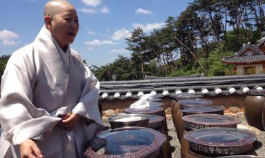 La venerabile monaca buddistaGye-Hodavanti a decine di onggi, i recipienti della tradizione coreana che contengono alimenti fermentati e marinati. E' il momento più emozionante della nostravisita al tempio di Jingwansa, alle porte di Seul. Una giornata dedicata a scoprire i segreti millenari della cucina buddista coreana