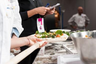 """Una tecnica inaspettata, la sua, dove tutti gli ingredienti vengono miscelati insieme, formaggio incluso (Grana Padana e formaggi italiani e americani) in modo da avere una cottura più omogenea. Propone una pizza """"al falso pesto"""" con un impasto di farine americane biologiche (un panetto di pasta pesa 400 grammi perché la pizza è intesa per due persone) condita con spinaci, asparagi, piselli, burro, sale ed erbe aromatiche che richiamano il colore verde e il gusto della nota salsa ligure. Molto bella da vedere ma forse lontana da ciò a cui noi siamo abituati a mangiare sulla pizza. Per questa occasione è stata assistita da un professionista d'eccezione, il maestroFranco Pepe, da poco rientrato da Portland"""