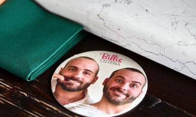 I gemelli Billi raffigurati in un sottobicchiere al bancone, perché la loro Osteria Billis a Tortona è anche un ottimo indirizzo per l'aperitivo. Ma noi siamo stati colpiti dall'ottima cucina, oltre che dall'atmosfera rilassata e informale