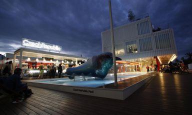 Un'immagine notturna dell'ingresso al padiglione della Repubblica Ceca, con la piscina, il bar e la grande scultura che depura l'acqua della fontana