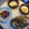 Arriva un secondo seafood platter. E' composto da: Oloturia e panna acida in diverse consistenze, anche tipo «chicharrones» (ore 9), sea urchin , ricci di mare (ore 12 e 3) e gigas oyster, ostrica gigante (ore 6)