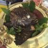 La Testa di dotto grigliatache può capitare di trovarealLido 84di Gardone Riviera (Brescia). Riccardo Camanini ha la fortuna di conoscere due pescatori del golfo di Oristano che pescano in profondità, con le palamite. Quando va bene gli mandano questi dotti (stessa famiglia della cernia)di pezzature esagerate.  La testa del pesce -piuttosto grassa ericca di carne nella guancia, nel sottogola e negli interstizi delle cervella - viene grigliata lentamente e servita intera al tavolo. Accanto c'è un piatto cosparso di colatura di alici, olio extravergine d'oliva, fegato disidratato dello stesso pesce e unagrattata di limone e rafano. Intingercii pezzi di dotto è un gesto arcaico che riconcilia col mondo.